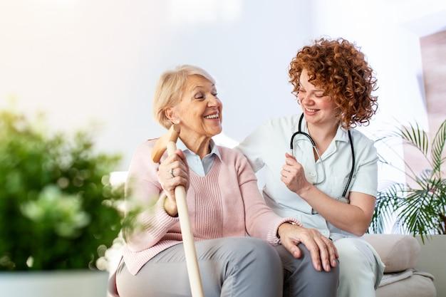 Vriendelijke relatie tussen glimlachende verzorger in uniform en gelukkig oudere vrouw. ondersteunende jonge verpleegster die hogere vrouw bekijkt.