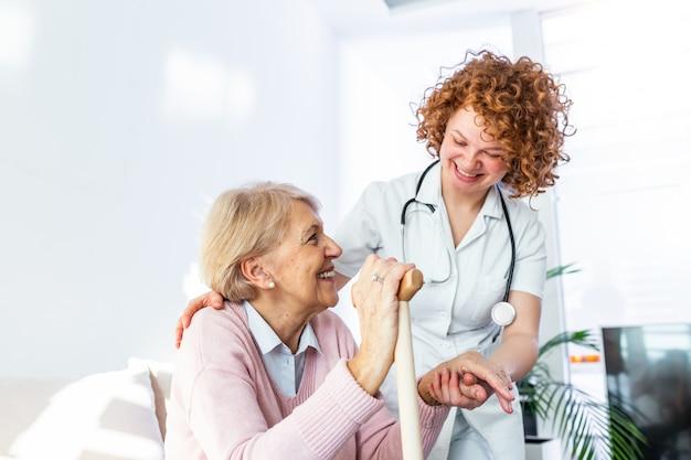Vriendelijke relatie tussen glimlachende verzorger in uniform en gelukkig oudere vrouw.