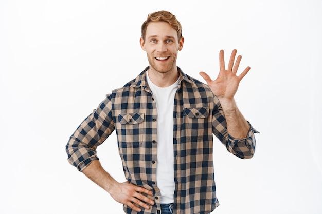 Vriendelijke roodharige man die met de hand naar je zwaait en gelukkig glimlacht, mensen begroet, iemand verwelkomt, tegen een witte muur staat