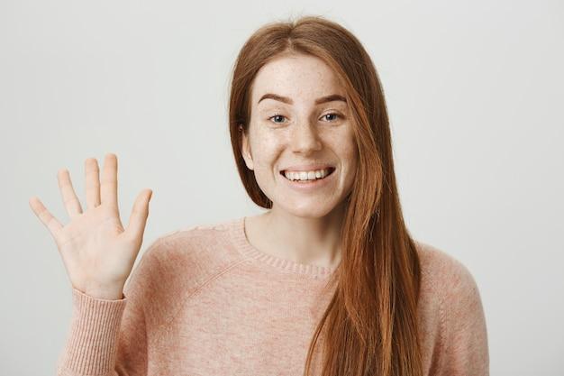 Vriendelijke roodharige meisje zwaaiende hand om gedag te zeggen, groet