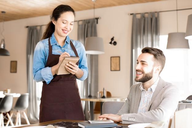 Vriendelijke serveerster die bestelling van klant opneemt