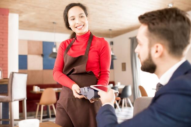 Vriendelijke serveerster die de betaling van de gast accepteert