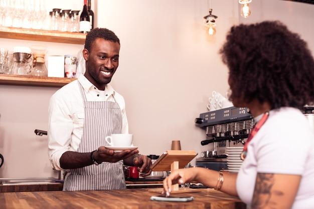 Vriendelijke service. opgetogen aardige man die naar de klant glimlacht terwijl hij koffie voor haar klaarmaakte