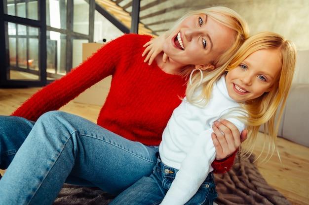 Vriendelijke sfeer. gelukkig meisje dat haar moeder omhelst terwijl ze thuis samen is