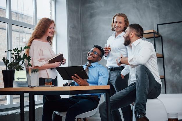 Vriendelijke sfeer. groep multiraciale kantoormedewerkers in formele kleding praten over taken en plannen
