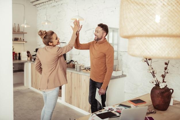 Vriendelijke sfeer. twee gelukkige collega's glimlachen en geven elkaar een high-five terwijl ze in de keuken staan.