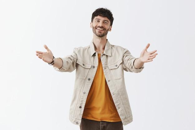 Vriendelijke stijlvolle bebaarde man poseren tegen de witte muur
