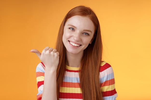 Vriendelijke tedere vrouwelijke soort roodharige vrouw blauwe ogen wijzende duim links tonen locatie waar vind product kopie ruimte graag helpen bespreken interessante promo grijnzende flirterige, oranje achtergrond.