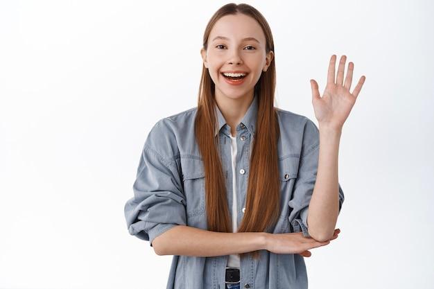 Vriendelijke tienerstudent, meisje zegt hallo, zwaaiend met de hand, heet je welkom, maak hallo gebaar, lach positief, staande over witte muur