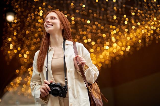 Vriendelijke trendy jonge roodharige vrouw met camerawandeling in de stad, boce op de achtergrond