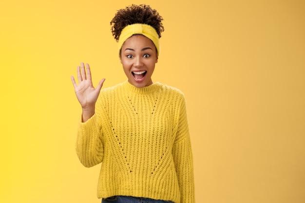 Vriendelijke uitgaande opgewonden schattige millennial vrouwelijke collega newbie begroetingsteam zwaaiend met palm hallo hallo gebaar energiek leer nieuwe mensen kennen die vrienden verwelkomen, staande gele achtergrond.