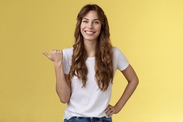Vriendelijke uitgaande vrolijke europese schattige vrouw die tips geeft die richting tonen levendig glimlachend toothy heb gelukkig een leuk aangenaam gesprek wijzend naar links duim introduceren promo gele achtergrond