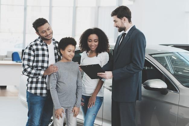 Vriendelijke verkoper houdt papieren gezin koopt auto