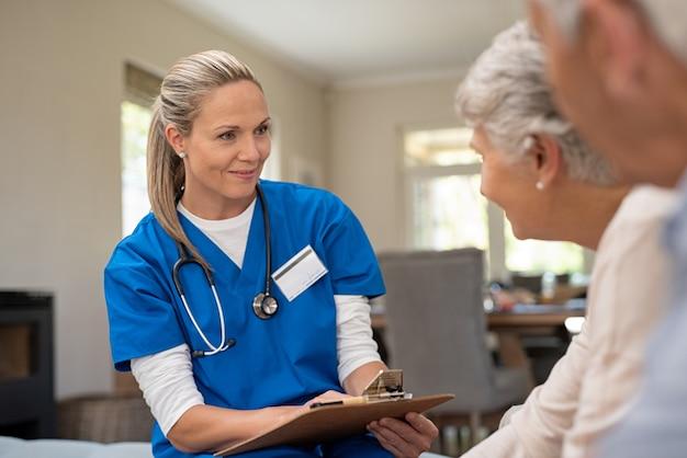 Vriendelijke verpleegster praten met oude paar
