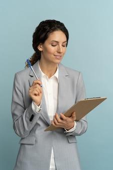 Vriendelijke verzekeringsagent vrouw draagt ?? grijze blazer met klembord, pen kijken naar documenten, studio.