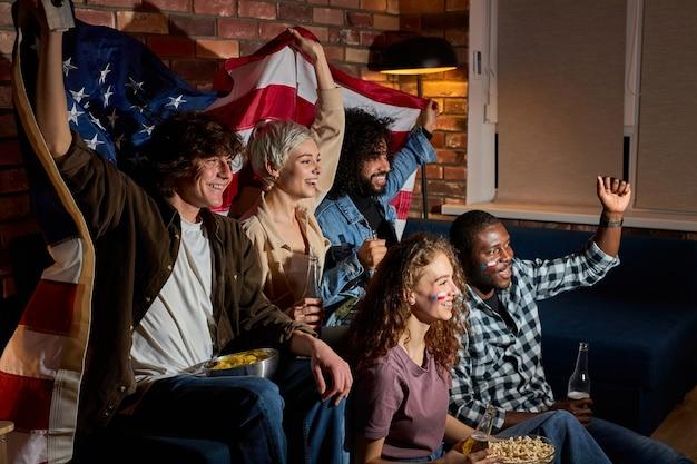 Vriendelijke voetbalfans verzamelden zich om te juichen tijdens het kijken naar voetbal of andere sportwedstrijden thuis, vrienden die naar het tv-scherm kijken juichen, plezier hebben, hun favoriete team steunen