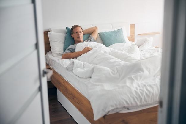 Vriendelijke volwassen mannelijke persoon die diep in gedachten is terwijl hij geniet van zijn luie ochtend
