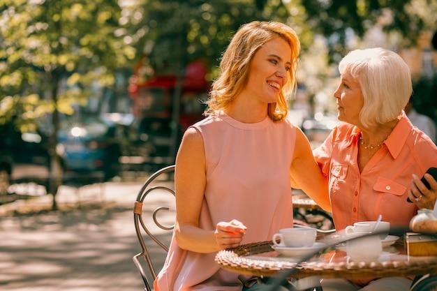 Vriendelijke volwassen vrouw die dicht bij haar moeder in café zit en glimlacht. websitebanner