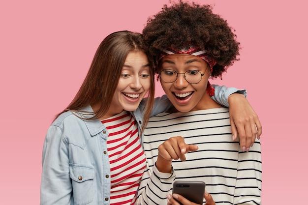 Vriendelijke vriendinnen hebben samen plezier, omhelzen elkaar en kijken naar grappige video op mobiel
