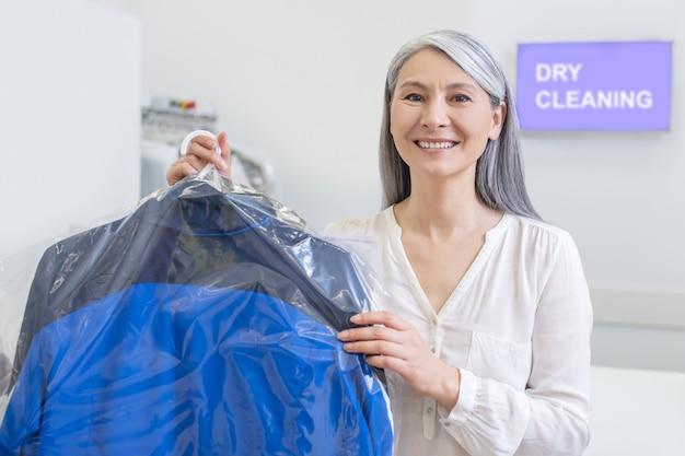Vriendelijke vrolijke vrouw met lang grijs haar met schone ingepakte kleren in hand in de stomerij