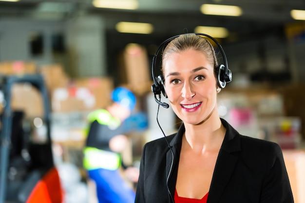 Vriendelijke vrouw, coördinator of supervisor die de headset gebruikt in het magazijn van het expeditiebedrijf,