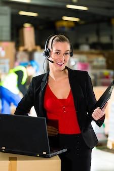 Vriendelijke vrouw, coördinator of supervisor met behulp van headset en laptop in magazijn van expeditiebedrijf,