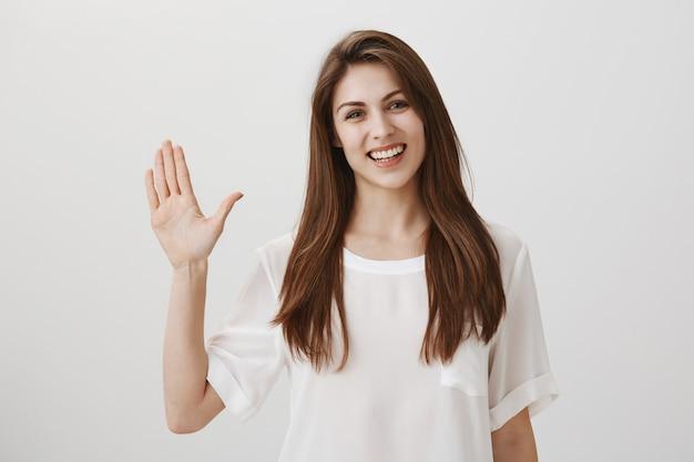 Vriendelijke vrouw zwaaiende hand om hallo te zeggen, gast groet