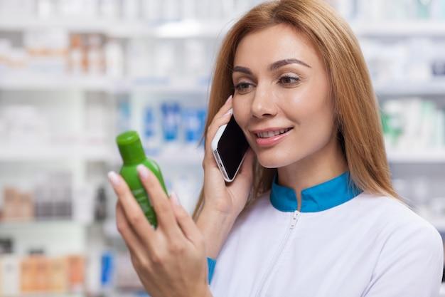 Vriendelijke vrouwelijke apotheker die telefonisch bestellingen ontvangt en bij de drogisterij werkt