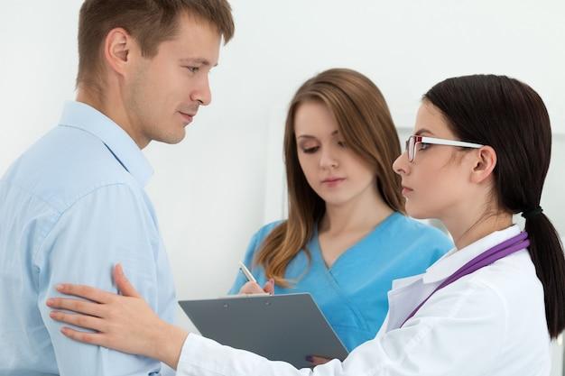 Vriendelijke vrouwelijke arts aan de arm van de mannelijke patiënt voor aanmoediging en empathie met haar collega verpleegster. partnerschap, vertrouwen en medische ethiek concept. minder slecht nieuws en ondersteuning.