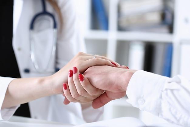 Vriendelijke vrouwelijke arts houdt mannelijke patiënt hand