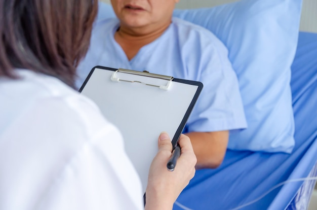 Vriendelijke vrouwelijke arts klembord houden en het controleren van oude patiënt liggend op bed in het ziekenhuis voor aanmoediging, virusuitbraak, quarantaine, herstel, ouderen, medische, gezondheidszorg concept