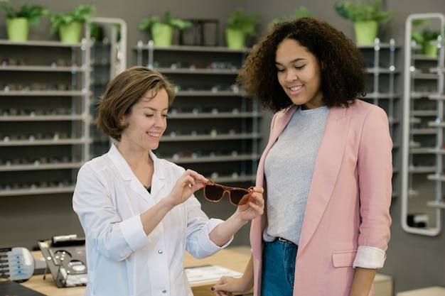 Vriendelijke vrouwelijke clinicus in whitecoat die nieuwe bril toont aan jonge vrouw van gemengd ras tijdens overleg