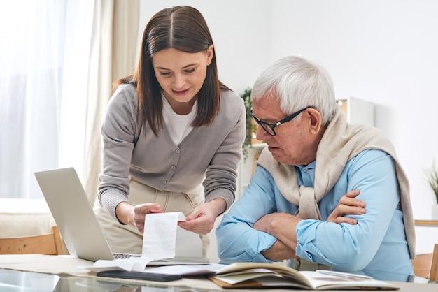 Vriendelijke vrouwelijke maatschappelijk werker cheque uitgaven uit te leggen aan senior man terwijl hij zijn budget analyseert