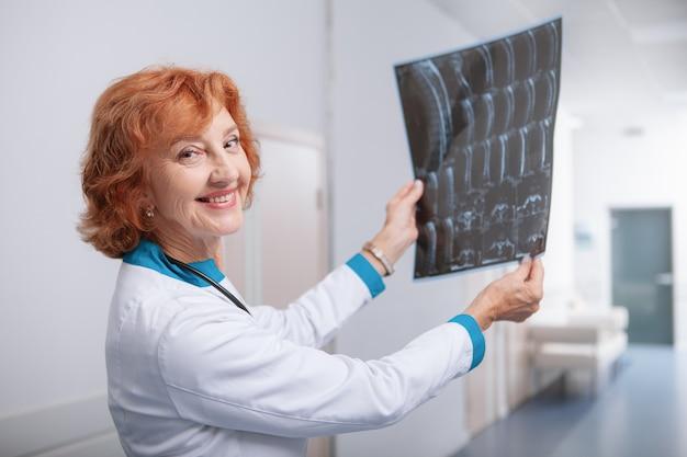Vriendelijke vrouwelijke oncoloog glimlachend naar de camera, met mri-scan van een patiënt