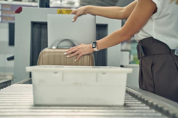 Vriendelijke vrouwelijke persoon die in halve positie staat terwijl ze haar gadget voor douanebeambte demonstreert