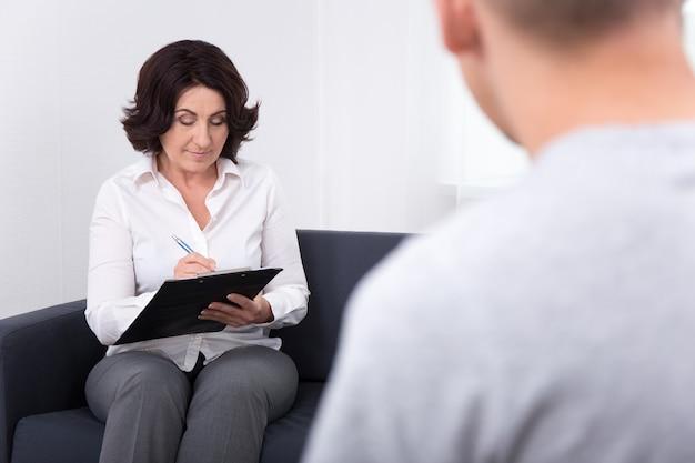 Vriendelijke vrouwelijke psychiater die met haar patiënt in een modern kantoor werkt