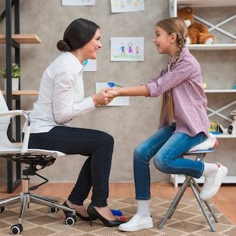 Vriendelijke vrouwelijke psycholoog hand in hand van een meisje bij therapie sessie
