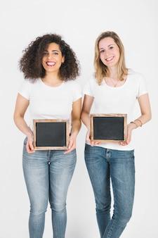 Vriendelijke vrouwen met schoolborden