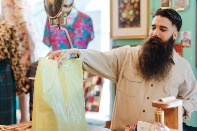 Vriendelijke winkelbediende handen een klant zijn tas in de kledingwinkel