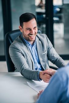 Vriendelijke zakelijke handdruk. het glimlachen van knap elegant mensenhandenschudden met werknemer.