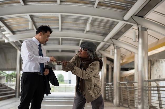 Vriendelijke zakenman geeft geld aan bedelaar