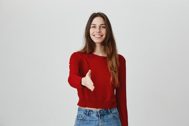 Vriendelijke zelfverzekerde vrouw stretch hand voor handdruk en lachend, groet persoon