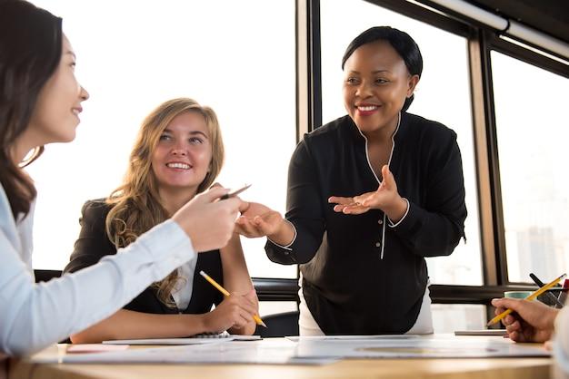 Vriendelijke zwarte zakenvrouw ter ondersteuning van haar collega in de vergadering