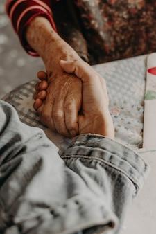 Vriendelijkheid. oude hand die een jonge hand houdt.
