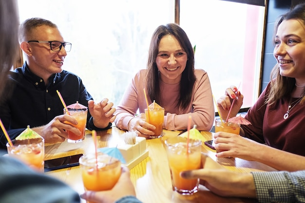 Vrienden aan de bar drinken een cocktail en hebben plezier