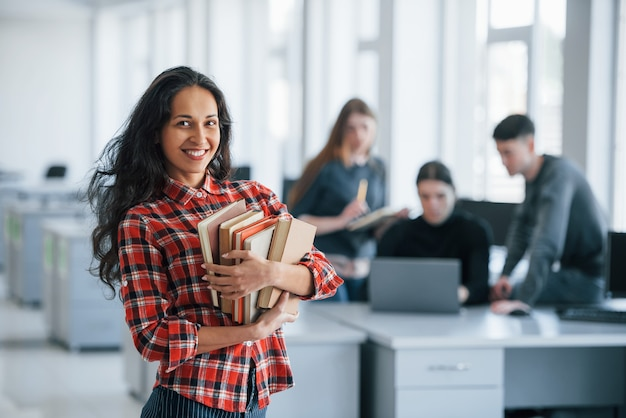 Vrienden achter. groep jonge mensen in vrijetijdskleding die in het moderne bureau werken