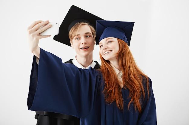 Vrienden afgestudeerden van de universiteit in caps glimlachen maken selfie.