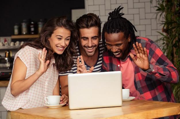 Vrienden begroeten iemand via het scherm van een laptop