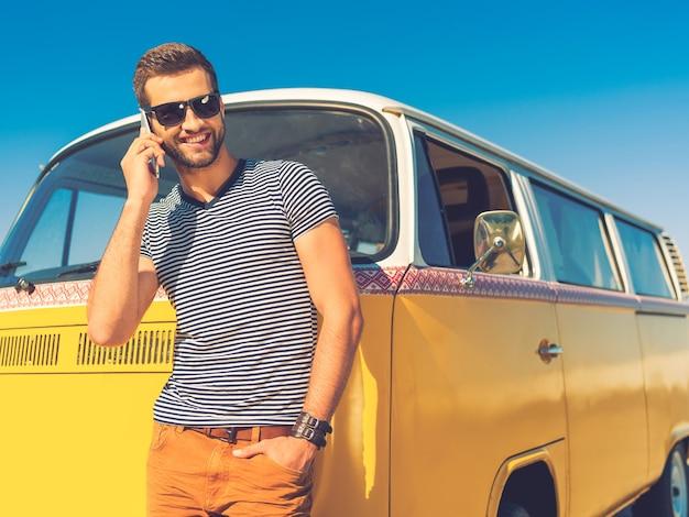 Vrienden bellen. gelukkige jonge man die op de mobiele telefoon praat en hand in zak houdt terwijl hij naar de retro minibus leunt