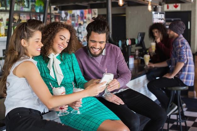 Vrienden bespreken via mobiel terwijl het hebben van een drankje in restaurant
